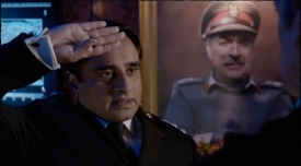 Colonel Ahmed salutes the Doctor in front of a portrait of the late Brigadier Lethbridge-Stewart