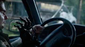 a hand comes out of a steering wheel