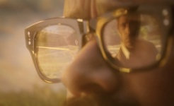 John reflected in Ritchie's glasses